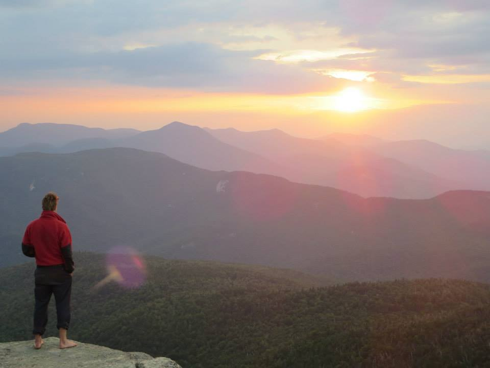 A crewmember looks out at the sunset from the summit of Mt. Chocorua