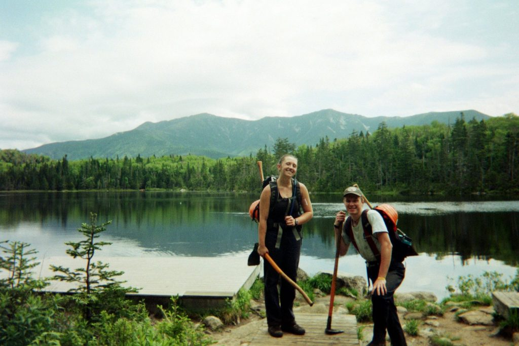 Two crewmembers pose for a photo at Lonesome Lake