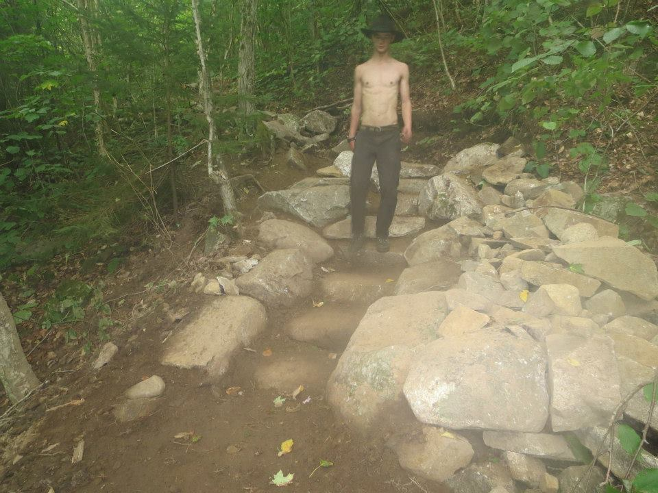 A crewmember walks over his newly constructed staircase on Champney Falls Trail