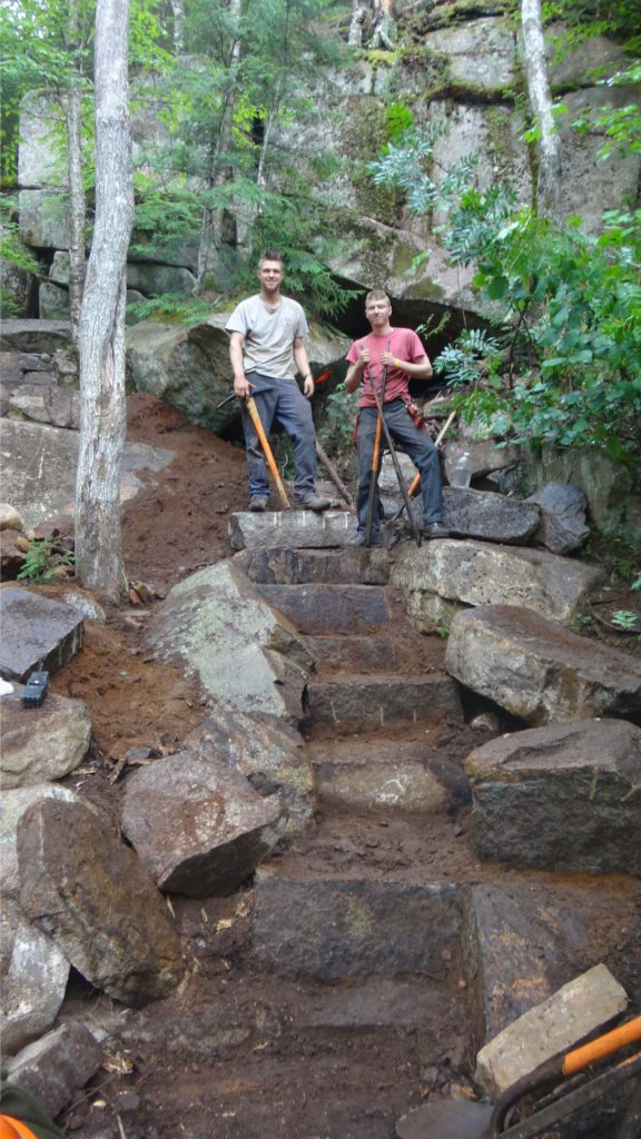 Two crewmembers stand atop a staircase still under construction. Champney Falls Trail